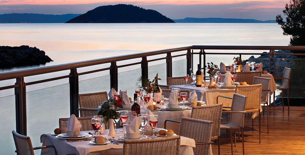 Betrachten Sie den romantischen Sonnenuntergang beim Abendessen