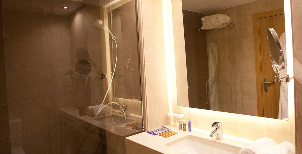 Accompagnée d'une salle de bain moderne et fonctionnelle