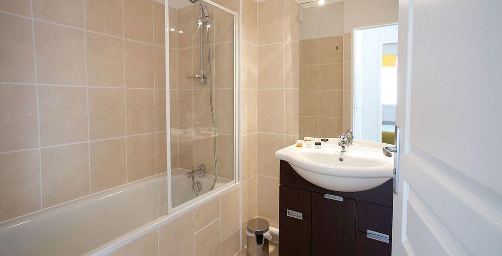 Une salle de bains avec baignoire ou douche...