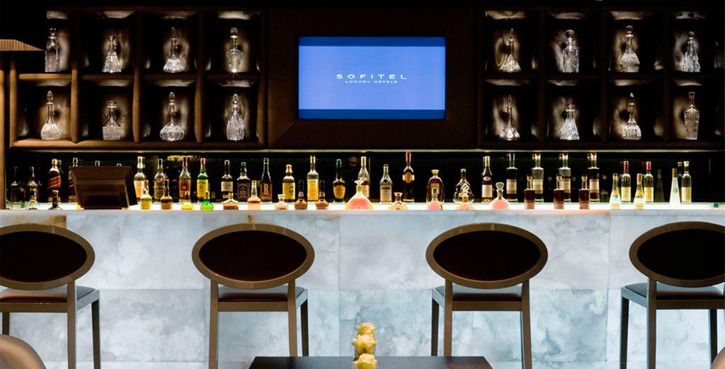 accomodarvi al bar dove mensole retro illuminate allineano decanter di cristallo fatti a mano