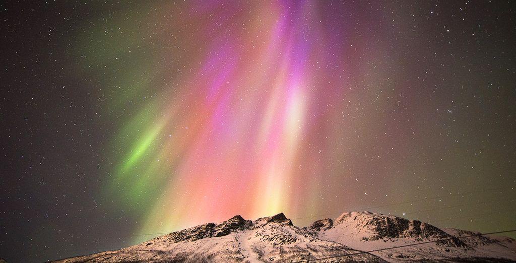 Fotografia delle montagne innevate della Norvegia e dell'aurora boreale