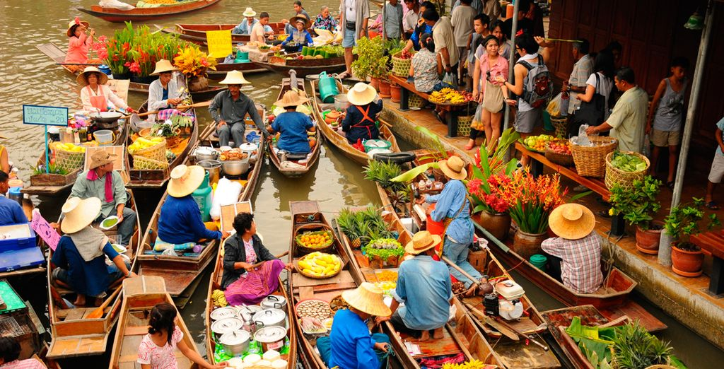 Watch the water market boats float along the river