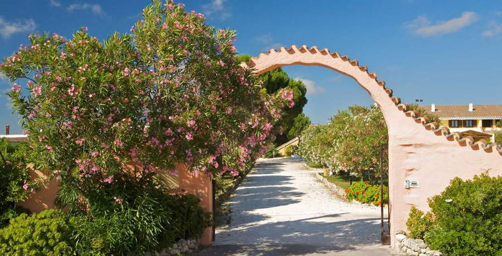 Walk through its idyllic entrance framed by nature - Is Benas Country Lodge 4* Sardinia