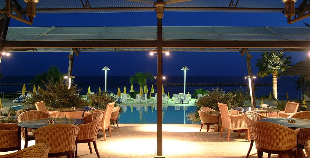 As night falls, enjoy a romantic dinner by the pool