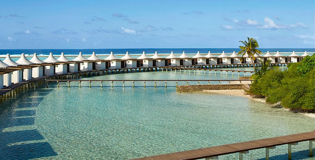 Your water bungalow is perched above the azure Indian Ocean...
